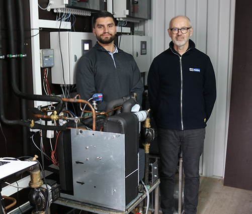Michael and Abdallah in front of a heat pump